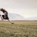 happy girl jumping in the air in the middle of a field