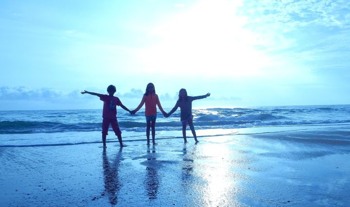 3 children holding hands on beach